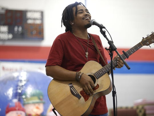 Royce Lovett plays an original song for the crowd at the Walker-Ford Community Center during a Christmas celebration. Working with Lovett inspired Matthew St. Fleur to found Journey Management in Tallahassee.