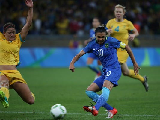 FILE - In this Aug. 12, 2016, file photo, Brazil's Marta, right, shoots as Australia's Katrina Gorry tries to block during a quarterfinal match of the women's Olympic football tournament between Brazil and Australia at the Mineirao Stadium in Belo Horizonte, Brazil. The Orlando Pride have signed five-time FIFA Women's World Player of the year Marta to a multi-year deal. The deal for one of the game's biggest stars had been rumored weeks before the Pride made it official on Friday, April 7, 2017.  (AP Photo/Eugenio Savio, File)