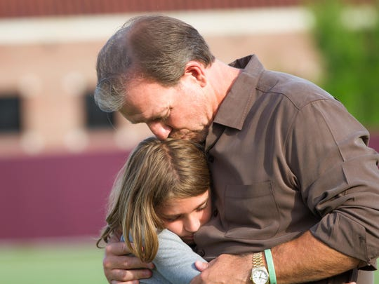 Jimbo Fisher and his youngest son, Ethan, hug on the FSU practice fields.