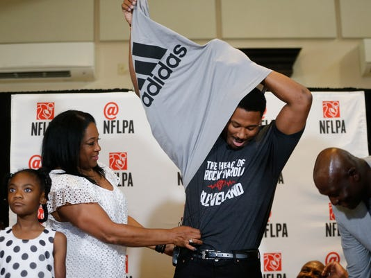 Texas A&M's Myles Garrett takes off his shirt to reveal a Cleveland Browns shirt while standing next to his mother, Audrey Garrett, left, after he was taken as the No. 1 pick in the NFL football draft, at Terre Verde Golf Course in Arlington, Texas, Thursday, April 27, 2017. (Nathan Hunsinger/The Dallas Morning News via AP)