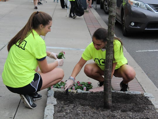 Taylor Breitzman, 18, and Olivia Craig, 18, of Saint Joseph High School plant flowers along Bellevue Avenue in Hammonton.