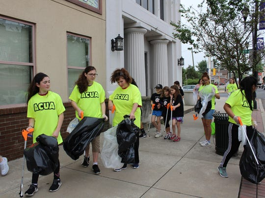 A group of volunteers begins the process of cleaning up Bellevue Avenue in Hammonton on Saturday, April 29.