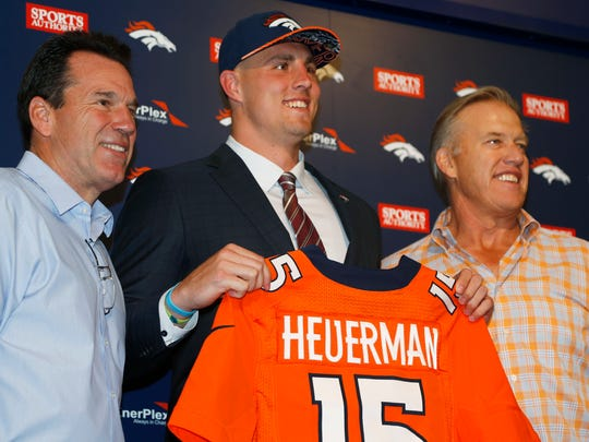 In this May 2, 2015, file photo, former Ohio State tight end Jeff Heuerman, center, the Denver Broncos third-round pick in the NFL Draft, holds up his new jersey while posing for a photograph with head coach Gary Kubiak, left, and general manager John Elway during a news conference.