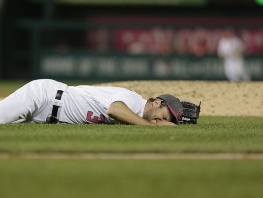 Washington Nationals starting pitcher Max Scherzer falls to the ground after being hit by a line drive in the fourth inning of the second game of a doubleheader against the Philadelphia Phillies, Sunday, May 14, 2017, in Washington. (AP Photo/Mark Tenally)