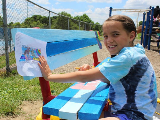 Anna Kolar of Edgewood sketches her drawing on the