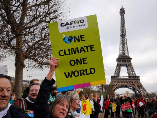 "FRANCOIS GUILLOT, AFP/Getty ImagesDemonstrators rally in Paris in December 2015 during the U.N. Climate Change Conference, where a pact signed by 180 nations was worked out. A demonstrator holds a banner reading ""One climate one world"" during a rally held by several Non Governmental Organisations (NGO) to form a human chain on the Champs de Mars near the Eiffel Tower in Paris on December 12, 2015 on the sidelines of the COP21, the UN conference on global warming. French hosts submit the final version of a global climate-saving pact to negotiators at UN Conference on december 12. The goal is for ministers to approve the agreement by the end of the day but that could be extended one more day. / AFP / FRANCOIS GUILLOTFRANCOIS GUILLOT/AFP/Getty Images ORIG FILE ID: 547225477"