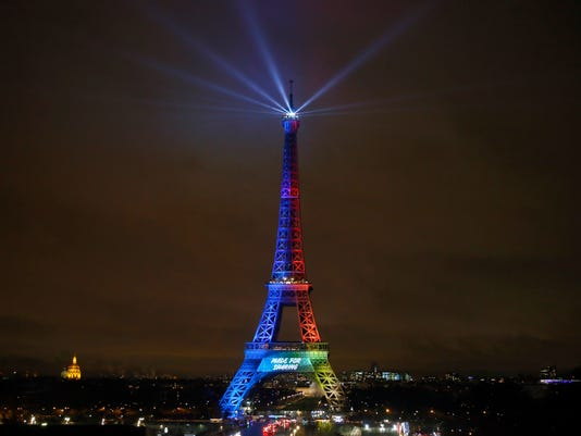"""FILE- In this Friday, Feb. 3, 2017 file photo, the Eiffel Tower is lit with colors for the Paris 2024 during the launch of the international campaign of Paris as candidate for the 2024 Olympic summer games in Paris. An International Olympic Committee panel has praised, Wednesday, July 6, 2017, Los Angeles and Paris for """"outstanding"""" plans to host the 2024 Summer Games. (AP Photo/Francois Mori, File)"""