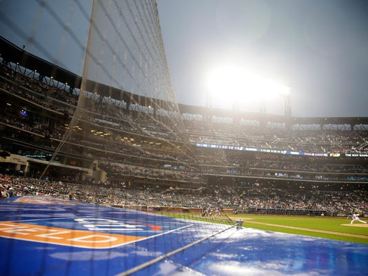 Fans watch through a net as New York Mets Jacob deGrom delivers a pitch during the third inning of a baseball game against the Colorado Rockies Friday, July 14, 2017, in New York. (AP Photo/Frank Franklin II)