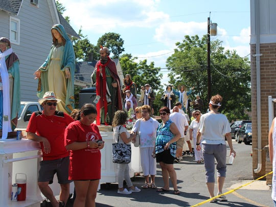 Volunteers line up the statues of the saints that will be carried through town behind Saint Joseph's Church before the procession.