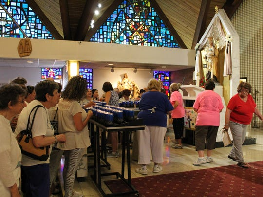 People light devotional candles to Our Lady of Mount Carmel inside Saint Joseph's Church before the start of the procession.