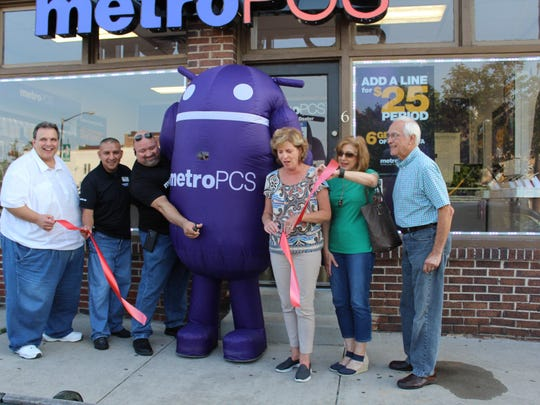 The relocated Metro PCS held a ribbon-cutting ceremony during the August Third Thursday with (left to right) Mayor Steve DiDonato, employee Juan Perez, District Manager Pete Castillo, the Metro PCS mascot, Cassie Iacovelli, executive director of MainStreet, Hammonton, Mainstreet Volunteer Kathy Bucknam and John Runfolo of the Greater Hammonton Chamber of Commerce.