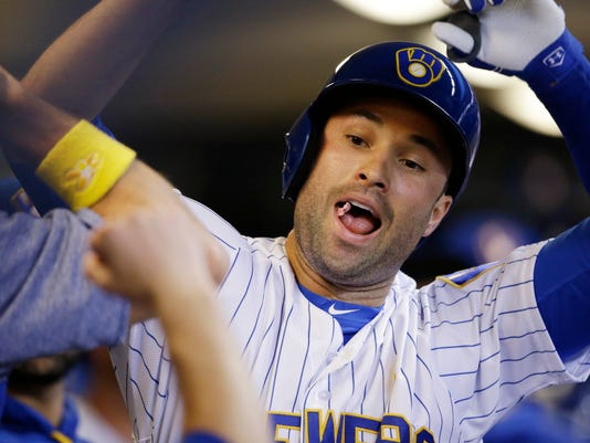 Milwaukee Brewers' Neil Walker celebrates in the dugout after his home run against the Washington Nationals during the first inning of a baseball game Friday, Sept. 1, 2017, in Milwaukee. (AP Photo/Jeffrey Phelps)