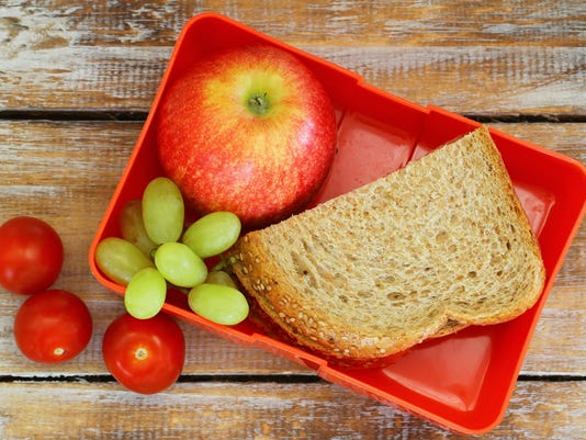 Lunch box with brown bread sandwich, apple, grapes and tomatoes
