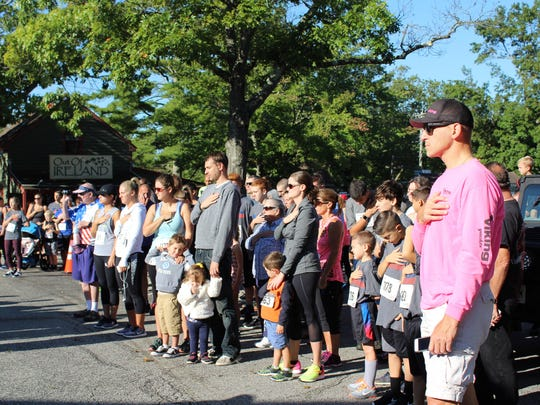 Runners, family and friends place their hands over their hearts during the national anthem.