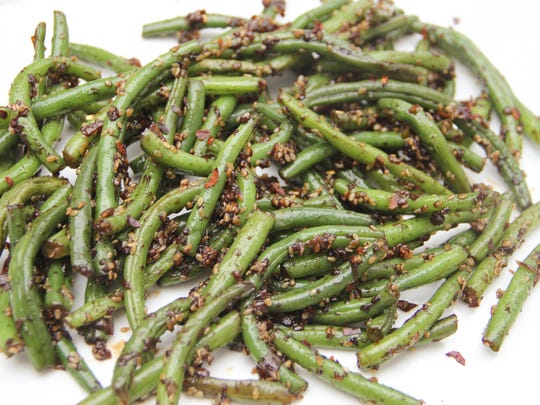 Green beans are spiked with garlic, red pepper, ginger and soy sauce. Melissa d'Arabian/AP