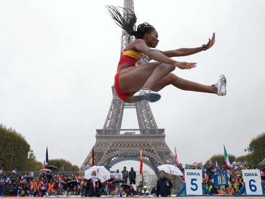 Nigerian-born Spanish athlete Juliet Itoya performs a high jump in front of the Eiffel Tower ahead of the vote in Lima, Peru, awarding the 2024 Games to the French capital, on the Champs de Mars garden in Paris, France, Wednesday, Sept. 13, 2017. Paris is certain of getting the 2024 Olympics so it has been able to plan its celebrations in advance. The International Olympic Committee is expected to confirm the award later Wednesday. (AP Photo/Thibault Camus)