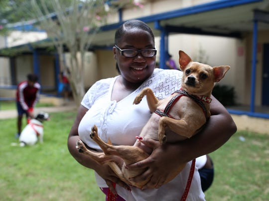 Monae Williams holds her dog Skippy at the Red Cross emergency shelter at Rickards High School Sunday. Lots of evacuees brought their pets.