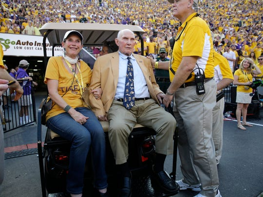FILE - In this Sept. 20, 2014, file photo, NFL great and LSU alumnus Y.A. Tittle, center, arrives in Tiger Stadium in the first half of an NCAA college football game between LSU and Mississippi State, in Baton Rouge, La. Tittle, the Hall of Fame quarterback and 1963 NFL Most Valuable Player, has died. He was 90. His family confirmed to LSU, where Tittle starred in college, that he passed away. No details were immediately provided. (AP Photo/Gerald Herbert)