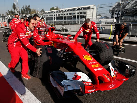 Mechanics push the car of Ferrari driver Kimi Raikkonen, of Finland, during the first practice session, prior to Sunday's Mexico Grand Prix, at the Hermanos Rodriguez racetrack in Mexico City, Friday, Oct. 27, 2017. (AP Photo/Moises Castillo)