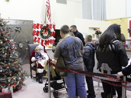 There was a line of eager children waiting to see Santa in the Wells Fargo bank after the tree lighting on Saturday evening.