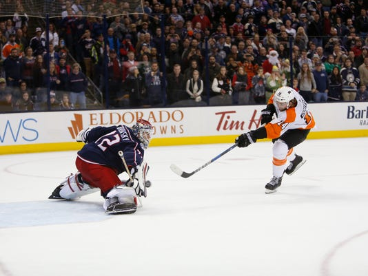 Columbus Blue Jackets' Sergei Bobrovsky, left, of Russia, makes a save against Philadelphia Flyers' Sean Couturier during the shootout period of an NHL hockey game Saturday, Dec. 23, 2017, in Columbus, Ohio. The Blue Jackets beat the Flyers 2-1 in a shootout. (AP Photo/Jay LaPrete)