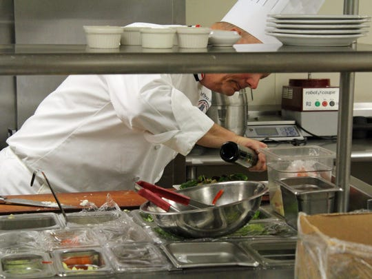 Bruce Johns, head chef of Careme's, puts the finishing touches on a guest's meal.