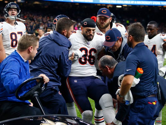 """FILE - In this Oct. 29, 2017, file photo, Chicago Bears tight end Zach Miller (86) is placed on a cart after injuring his leg in the second half of an NFL football game against the New Orleans Saints in New Orleans. For the Super Bowl, there is an Emergency Action Plan, an exhaustive outline that describes who does what in virtually every case of injury or emergency. It's so detailed that it includes arm or hand signals to help all involved determine what action is needed. """"The collaborative effort between teams is where it should be ... seamless and flawless,"""" said Vikings head athletic trainer Eric Sugarman. The emphasis, of course, is on immediate treatment whenever an injury occurs. The hour-long meeting's value became apparent when Miller dislocated his left knee and tore an artery that supplies blood to the lower leg. Miller could have lost the leg had it not been for the quick action by the well-schooled medical staffs. (AP Photo/Butch Dill, File)"""