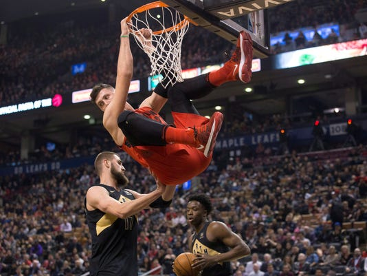 Portland Trail Blazers' Jusuf Nurkic hangs from the rim after scoring as Toronto Raptors Jonas Valanciunas, left, prevents him from swinging back during first-half NBA basketball game action in Toronto, Friday, Feb. 2, 2018. (Chris Young/The Canadian Press via AP)