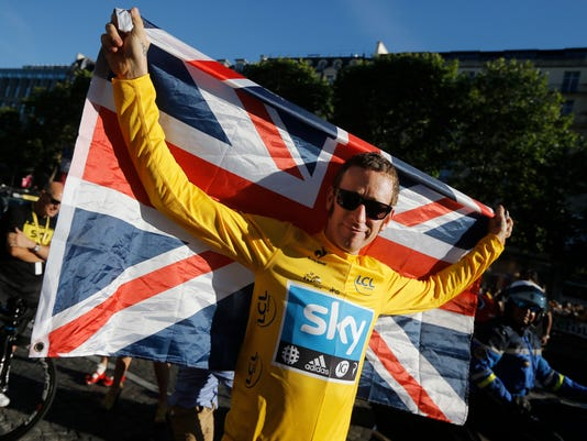 "FILE - In this Sunday, July 22, 2012 file photo, Bradley Wiggins, winner of the 2012 Tour de France cycling race, holds the Union flag during the team parade of the the Tour de France cycling race in Paris, France. A British parliamentary committee says in a doping investigation report that Bradley Wiggins used a banned powerful corticosteroid to enhance his performance and not for medical reasons while winning the Tour de France in 2012. The report accuses Team Sky of crossing an ""ethical line"" after preaching zero tolerance. Team Sky criticized ""the anonymous and potentially malicious claim"" by members of parliament. (AP Photo/Laurent Cipriani, File)"