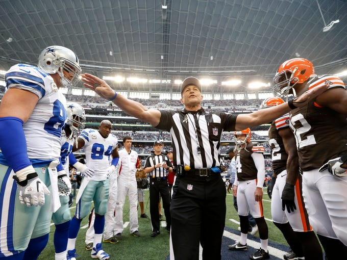 Referee Ed Hochuli (85) with Dallas Cowboys and Cleveland Browns team captains during the coin toss before an NFL football game Sunday, Nov. 18, 2012, in Arlington, Texas. The Cowboys won in overtime 23-20. (AP Photo/Sharon Ellman) ORG XMIT: OTKTG223