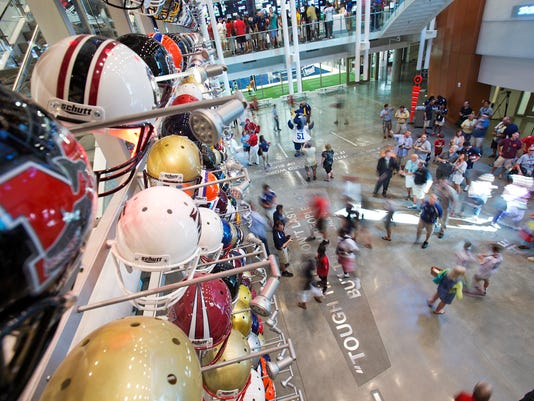 "FILE - In this Aug. 23, 2014, file photo, visitors walk through the lobby of the College Football Hall of Fame after its grand opening, Saturday in Atlanta. Peach Bowl president Gary Stokan says he still sees the College Football Hall of Fame as the hub of Atlanta's claim as the ""capital of college football,"" and his bowl has invested another $8 million in that vision. The Peach Bowl on Thursday, March 29, 2018, extended its partnership with the Hall of Fame for 10 years with the new investment which followed the original $5 million commitment when the hall opened in 2014.  (AP Photo/David Goldman, File)"