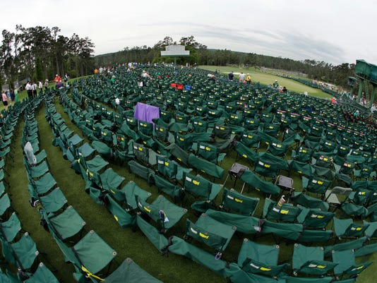 FILE - In this April 12, 2015, file photo, taken with a fisheye lens, empty chairs sit around the 18th green before the fourth round of the Masters golf tournament in Augusta, Ga. Patrons get to the Masters early, waiting outside the gates for the doors to open. They set up their chairs, then leave, walking to course to follow a certain golfer and when they come back, no one has moved their chair. (AP Photo/Matt Slocum, File)
