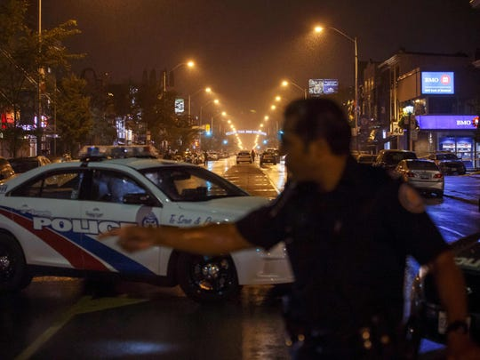 Toronto Police officers work on Danforth St., at the scene of a shooting in Toronto, Ontario, Canada on July 23, 2018. A gunman opened fire in central Toronto on Sunday night, injuring 13 people including a child.