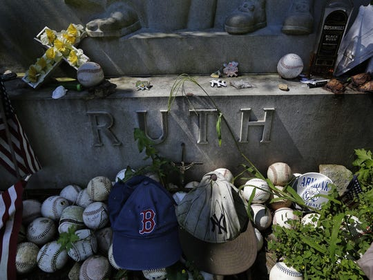 """Items left by visitors decorate the grave of George Herman """"Babe"""" Ruth and Claire Ruth at the Gates of Heaven Cemetery in Hawthorne, N.Y."""