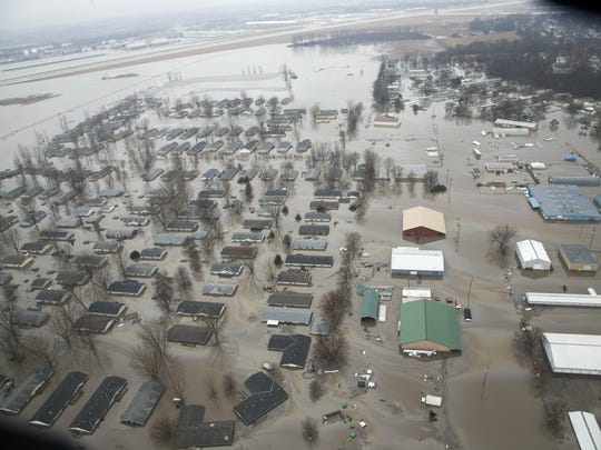 A neighborhood in Bellevue, Neb., is flooded by waters from the Missouri River, Tuesday, March 19, 2019, with the flooded runway of Offutt AFB seen top left.