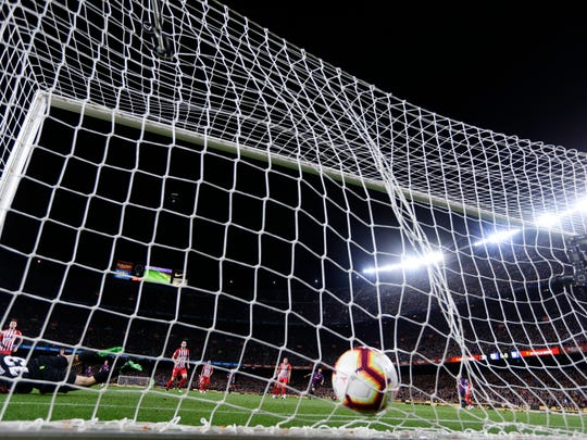 Atletico goalkeeper Jan Oblak, down left corner, fails to stop Barcelona forward Luis Suarez' shot on goal giving Barcelona a 1-0 lead during a Spanish La Liga soccer match between FC Barcelona and Atletico Madrid at the Camp Nou stadium in Barcelona, Spain, Saturday April 6, 2019. (AP Photo/Manu Fernandez)