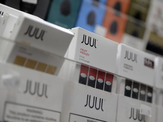 FILE - In this Dec. 20, 2018, file photo Juul products are displayed at a smoke shop in New York. Under scrutiny amid a wave of underage vaping, Juul is pushing into television with a multimillion-dollar campaign rebranding itself as a stop-smoking aid for adults trying to kick cigarettes. (AP Photo/Seth Wenig, File)