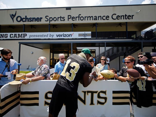 New Orleans Saints wide receiver Michael Thomas (13) signs autographs during training camp at their NFL football training facility in Metairie, La., Thursday, Aug. 1, 2019. (AP Photo/Gerald Herbert)
