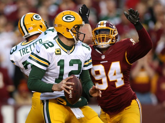 Quarterback Aaron Rodgers (12) of the Green Bay Packers is sacked for a safety by defensive end Preston Smith (94) of Washington in the first quarter during the NFC Wild Card Playoff game at FedExField on Jan. 10, 2016 in Landover, Maryland. Smith now plays for the Packers. (Photo by Patrick Smith/Getty Images)