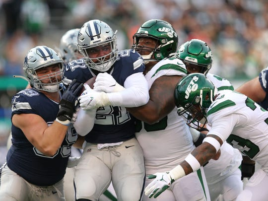 Dallas Cowboys running back Ezekiel Elliott (21) is stopped by New York Jets defensive tackle Steve McLendon (99) and safety Jamal Adams (33) during the second quarter at MetLife Stadium in East Rutherford, New Jersey, on Oct. 13, 2019.