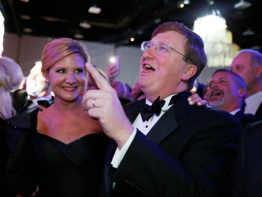 Gov. Tate Reeves and his wife, Elee Reeves, sing along with one of the inaugural ball performers Tuesday in Jackson, Miss.