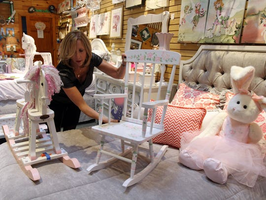Eileen Buriani, owner of Kidegories, arranges a display of custom painted and personalized items available in her store in Shrewsbury.