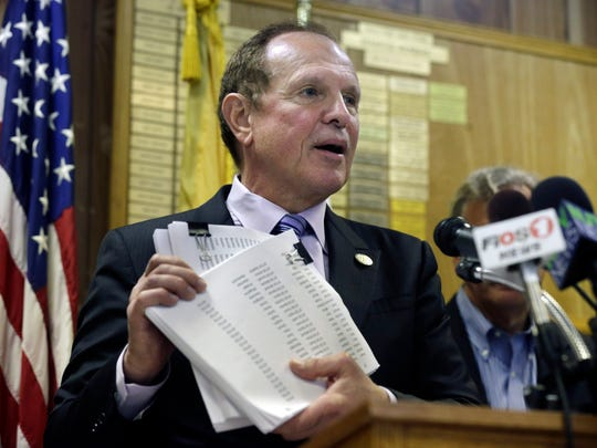 New Jersey Sen. Raymond J. Lesniak, D-Elizabeth, N.J., holds up petitions with over 15,000 signatures opposing New Jersey Gov. Chris Christie's proposed settlement with ExxonMobil Corp., in this April 7 file photo.