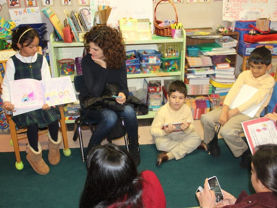 Aliza Riaz of Fanwood, a first-grader at The Wardlaw-Hartridge School in Edison, shares her book with classmates and parents at the First Grade Publishing Party on Dec. 12. The students selected a topic, wrote and illustrated pages to create their first published work. Parents were invited to the first grade classrooms to share in this special accomplishment.