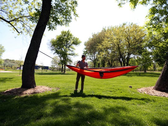 Zachary Gilbert of Des Moines demonstrates how to use a hammock that he has suspend ed between two trees at Gray's Lake Park.