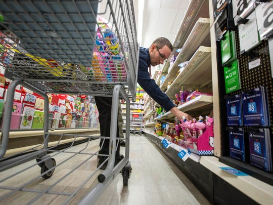 Scott Thrailkill, 39, sorts and straightens items on the shelves of a Kmart store on Hickman Road in Urbandale in 2015. The store closed this spring.