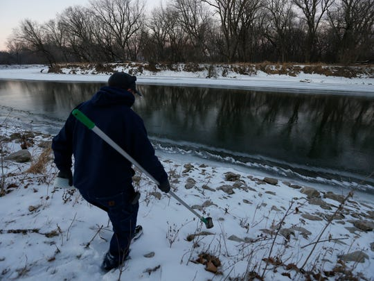 Bill Blubaugh, lab technician with Des Moines Water Works, heads down the riverbank of the Raccoon River Thursday to collect water samples that will be tested at the treatment plant in Des Moines.