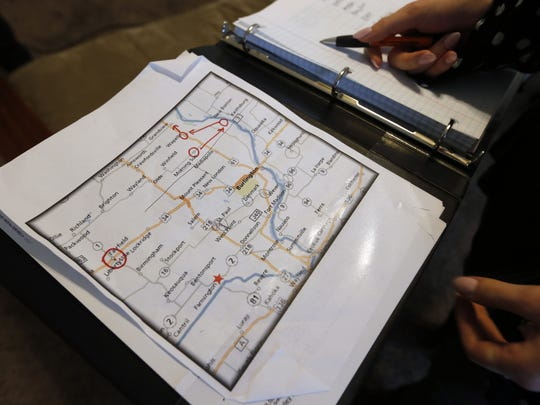 Kat Kanan shows the log book she and boyfriend Cody Weber are using to track the Iowa towns they have photographed Monday, April 13, 2015.