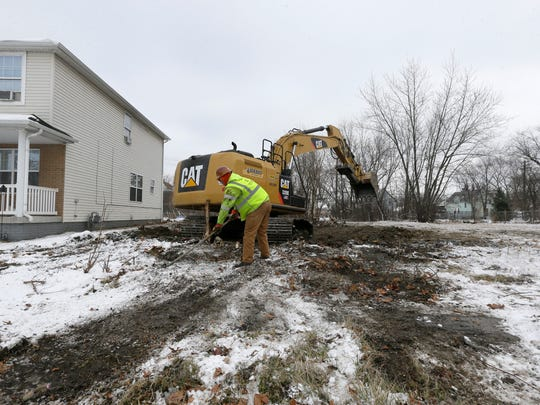 In a photo from, Thursday, Jan. 22, 2015, a crew from Adamo Demolition preps the site of a former vacant home for backfill in southwest Detroit.