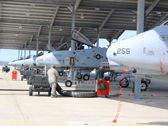 A row of A-10 fighter jets sit under a canopy at the